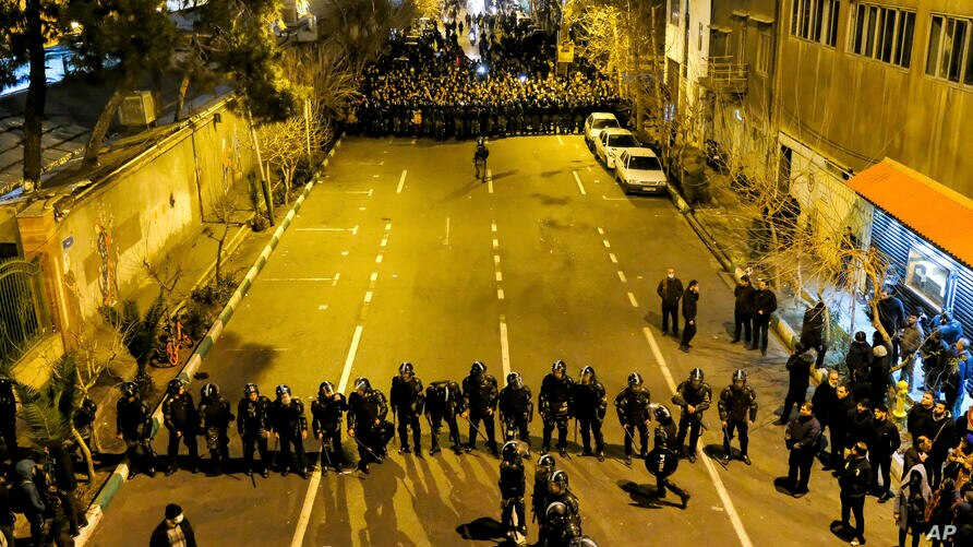 In this photograph taken Saturday, Jan. 11, 2020, Iranian police officers take position while protesters gather in front of…