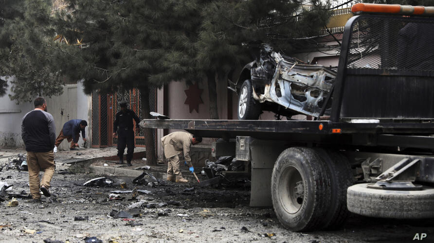 Security personnel inspect the site of a bomb attack in Kabul, Afghanistan, Saturday, Feb. 20, 2021. A few separate explosions…