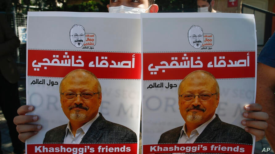 People hold posters of slain Saudi journalist Jamal Khashoggi, near the Saudi Arabia consulate in Istanbul, marking the two…
