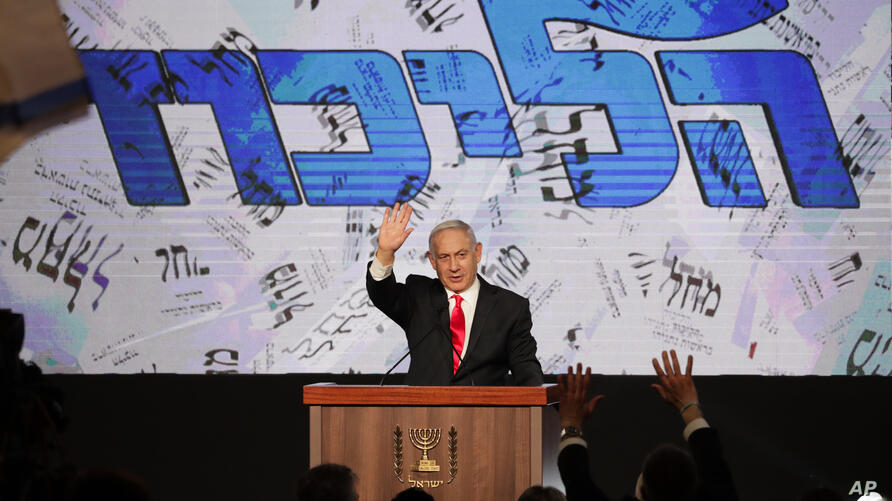 Israeli Prime Minister Benjamin Netanyahu waves to his supporters after the first exit poll results for the Israeli…