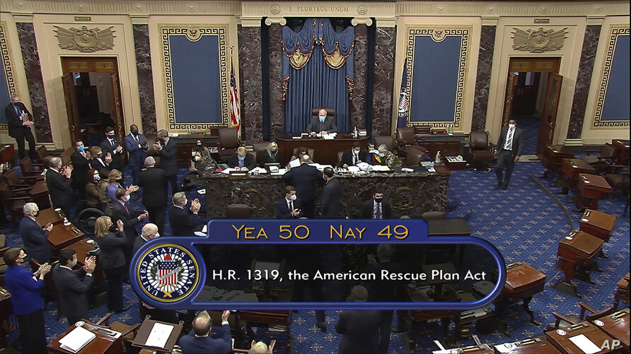 In this image from video, the vote total of 50-49 on Senate passage of the COVID-19 relief bill, is displayed on screen in the…