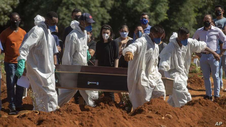 Cemetery workers in full protective gear carry a coffin that contains the remains of a person who died from complications…