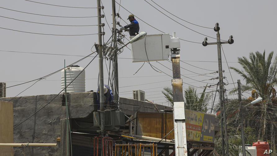Ministry of Electricity workers are trying to maintain the electricity transmission network in Basra, Iraq, Thursday, July. 30,…