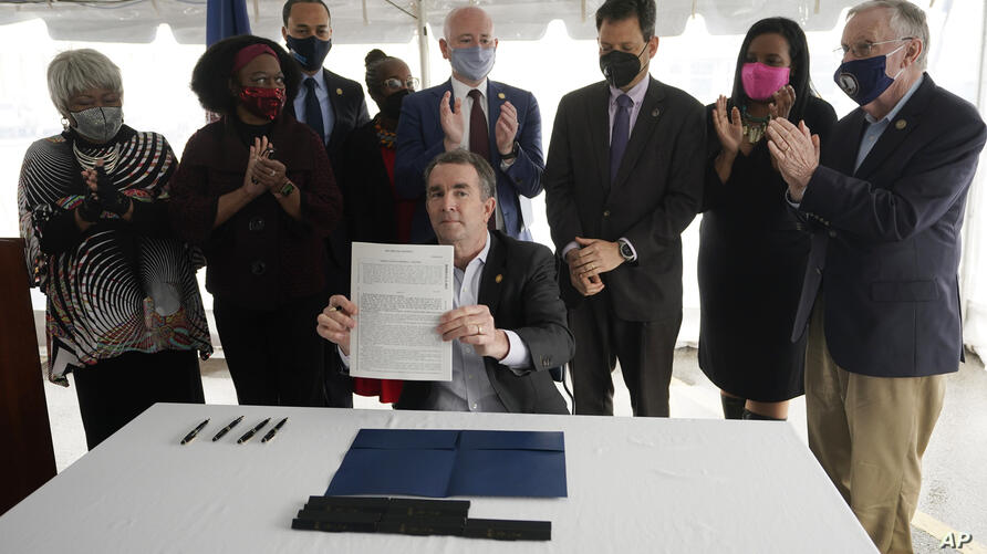Virginia Gov. Ralph Northam, seated center, displays a bill abolishing the death penalty after signing it as he is surrounded…