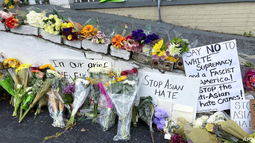 FILE - In this March 19, 2021, file photo, flowers, candles and signs are displayed at a makeshift memorial in Atlanta. A…