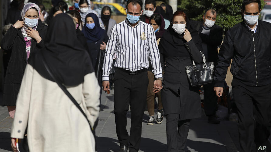 People wearing protective face masks to help prevent the spread of the coronavirus walk in downtown Tehran, Iran, Monday, April…