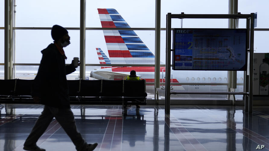 An American Airlines jet sits parked at a gate as light snow falls at Ronald Reagan Washington National Airport, Tuesday, Feb…