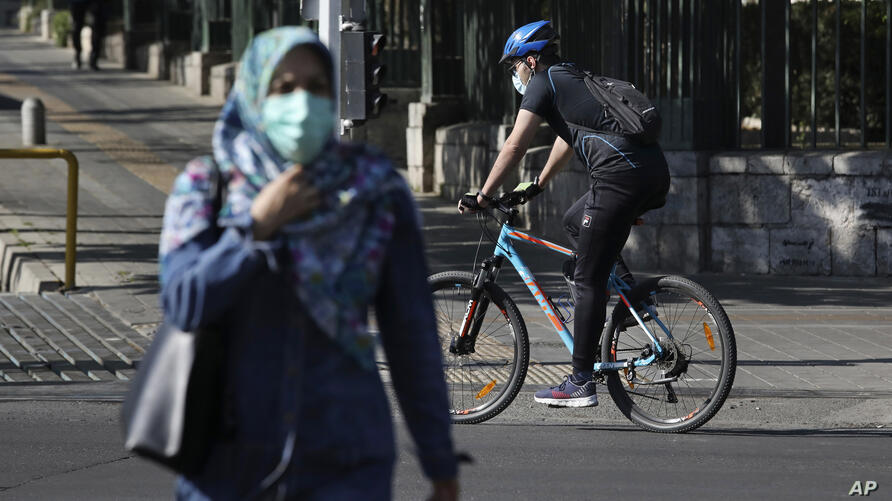 Wearing protective face masks to help prevent the spread of the coronavirus, a man rides his bicycle and a woman crosses a…
