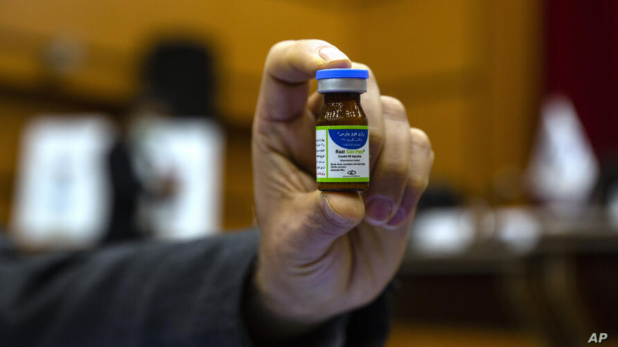 """An Iranian official holds a vial of an Iranian-made """"Razi Cov Pars"""" coronavirus vaccine during an unveiling ceremony at the…"""