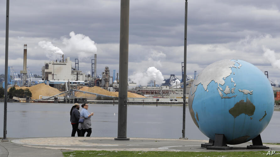 In this April 21, 2020 photo, people walk past an Earth globe sculpture at Thea's Park in Tacoma, Wash., with the WestRock…