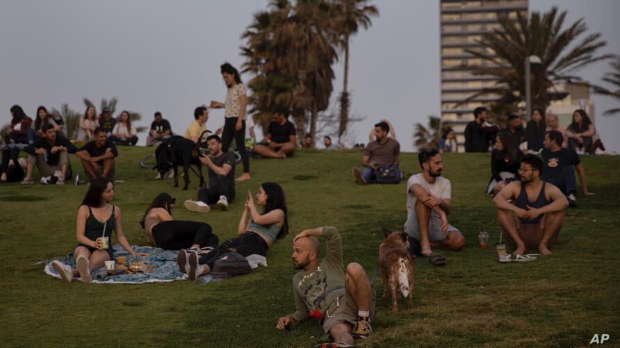 People without face masks watch the sunset, in Tel Aviv, Israel, Sunday, April 18, 2021. Israel has lifted a public mask…