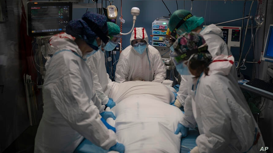 A medical team prepares to rotate a COVID-19 patient in the ICU of the Hospital del Mar, in Barcelona, Spain, Tuesday, Jan. 19,…