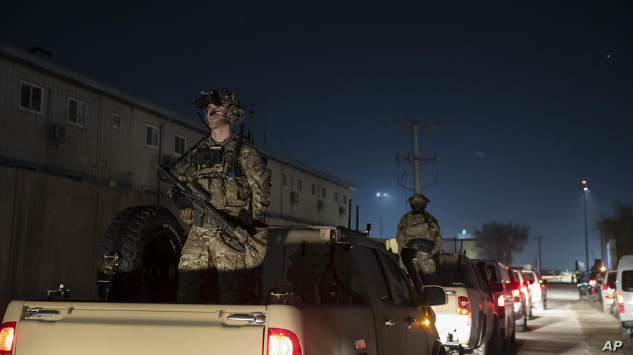 FILE - In this Nov. 28, 2019, file photo armed soldiers stand guard in the motorcade for President Donald Trump speaks during a…