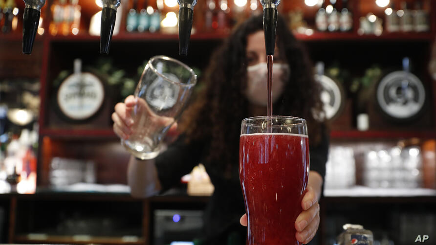 The first alcoholic drinks are poured for customers: two pints of cider at the Shakespeare's Head pub, which will be reopening…