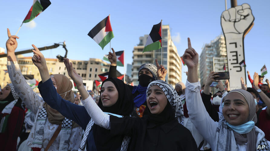 Lebanese and Palestinians chant slogans as they celebrate a cease-fire in Gaza, which is seen by many as a clear victory for…