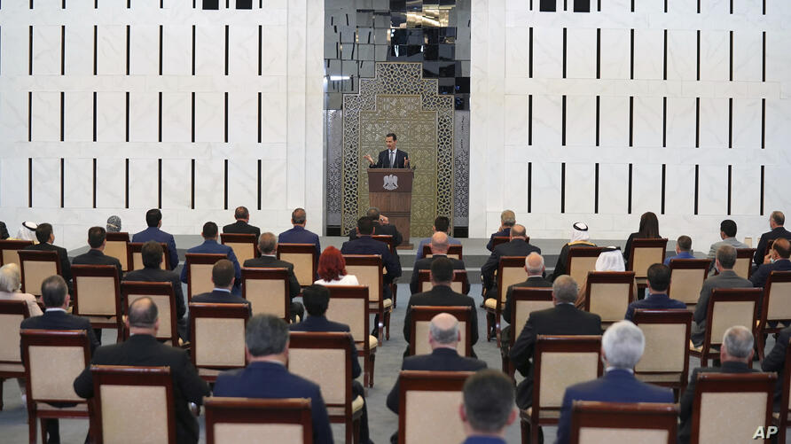 In this photo released by the Syrian official news agency SANA, Syrian President Bashar al-Assad addresses the parliament, in…