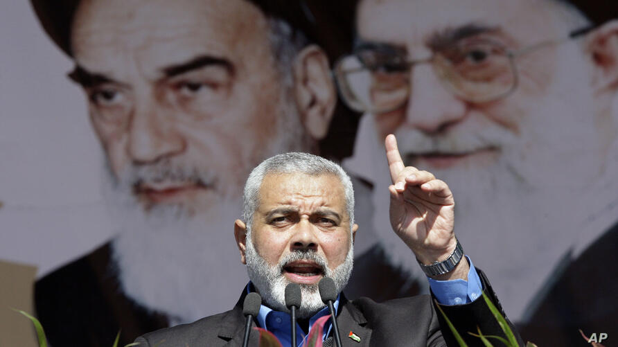 Visiting Hamas prime minister from Gaza, Ismail Haniyeh, gestures as he delivers his speech in front of portraits of late…