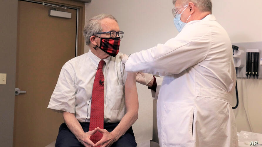 Ohio Gov. Mike DeWine, left, gets his first dose of the COVID-19 vaccine from Dr. Kevin Sharrett, Tuesday, 2, 2021, in…