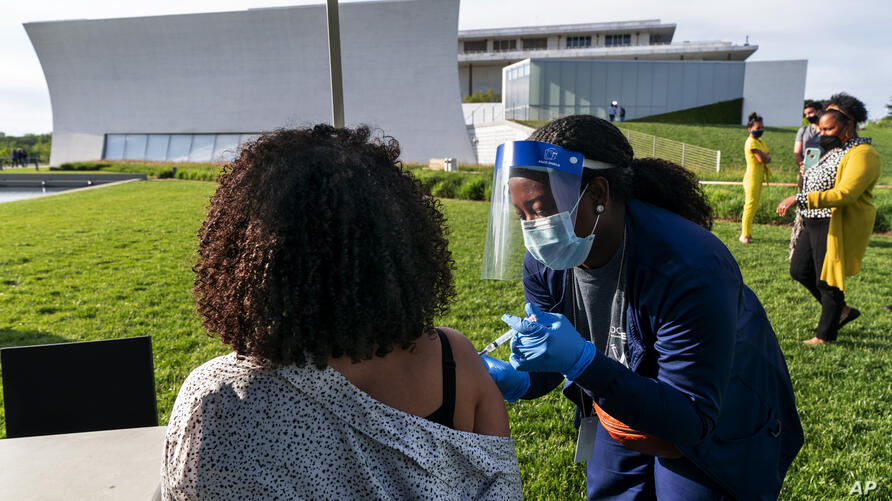FILE - In this May 6, 2021, file photo, Kendria Brown, a nurse with DC health, vaccinates a woman with the Johnson & Johnson…