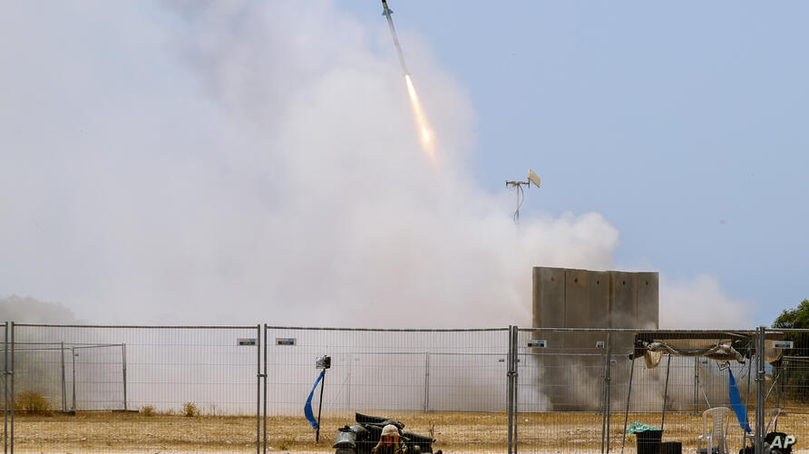 A Israeli soldier takes cover as an Iron Dome air defense system launches to intercept a rocket from the Gaza Strip, in…