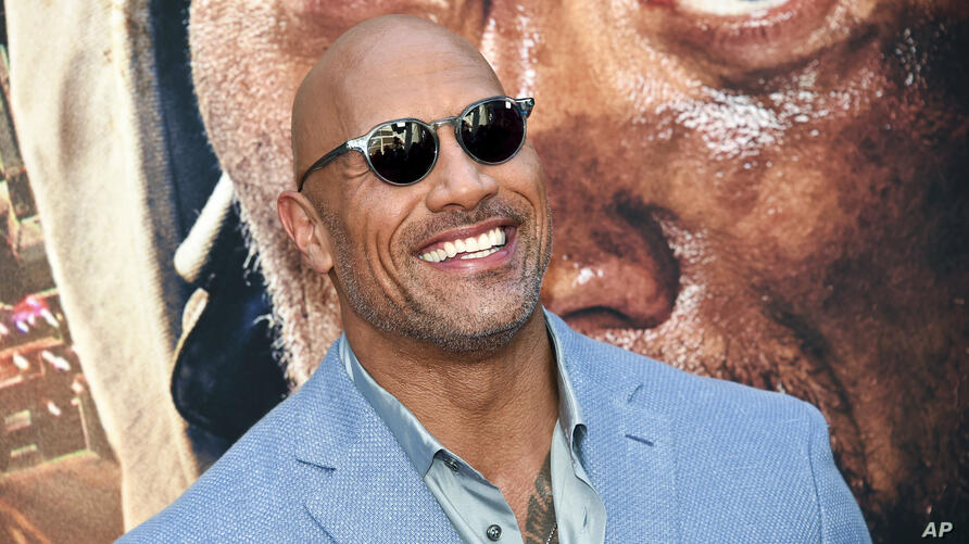 """FILE - In this July 10, 2018, file photo, Actor Dwayne Johnson attends the """"Skyscraper"""" premiere in New York. George Clooney…"""