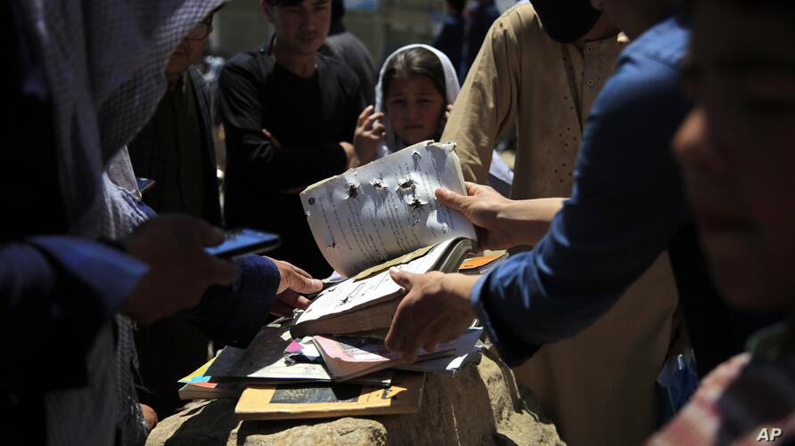 Afghans go through belongings left behind after deadly bombings on Saturday near a school in Kabul, Afghanistan, Sunday, May 9,…