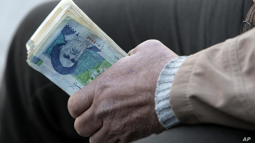 FILE- In this Thursday, Jan. 26, 2012 file photo, an Iranian street money changer holds Iranian banknotes with a portrait of…