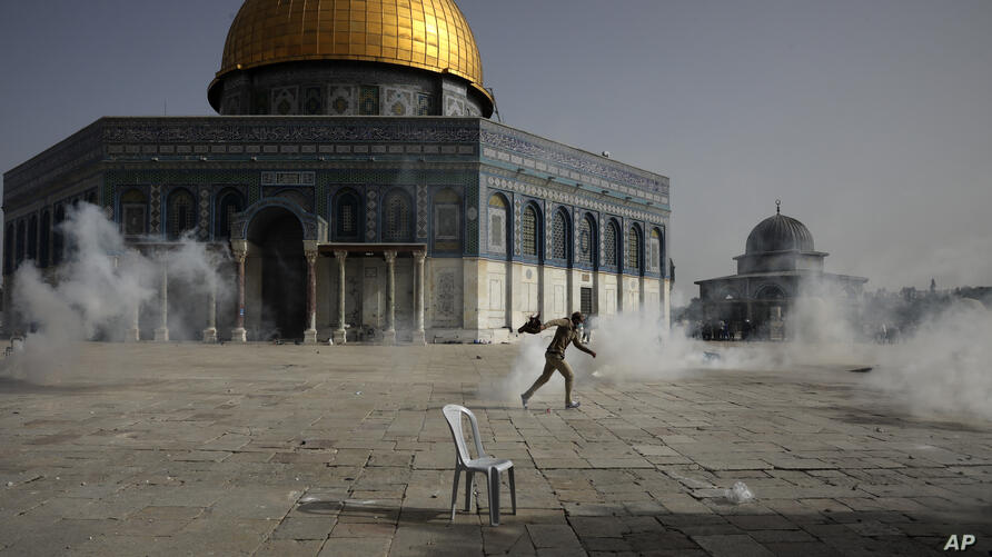 A Palestinian man runs away from tear gas during clashes with Israeli security forces in front of the Dome of the Rock Mosque…