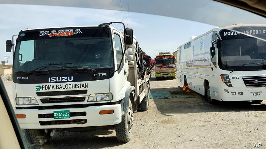 Mobile medical screening unit and cargo trucks park at the closed Pakistan-Iran border crossing,  Tuesday, Feb. 25, 2020, in…