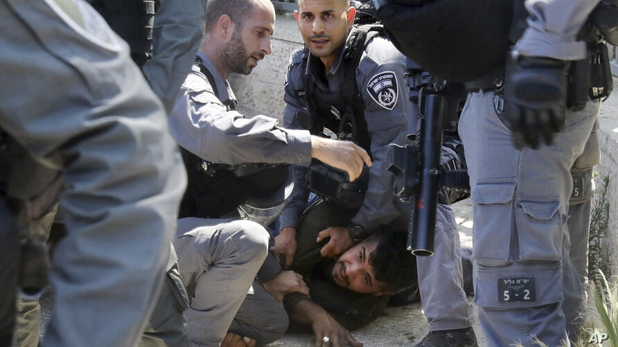 Israeli police officers detain a Palestinian man during clashes that erupted ahead of a planned march by Jewish…