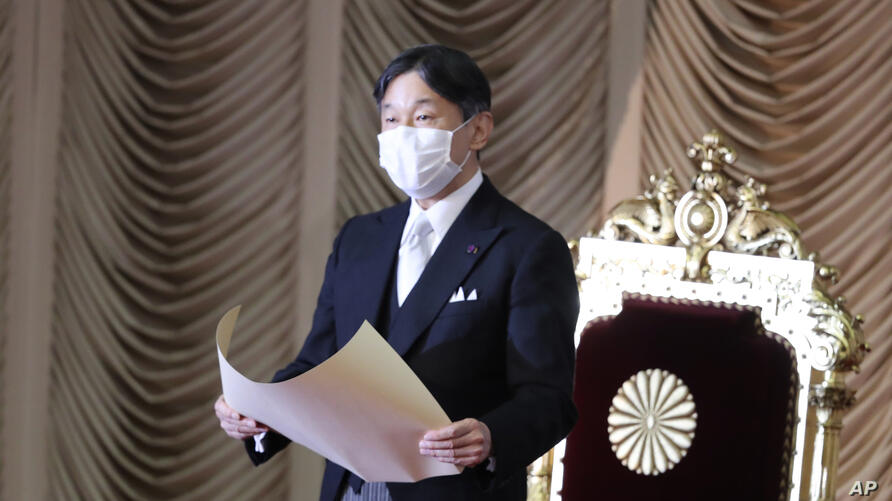 Japan's Emperor Naruhito wearing a face mask to protect against the coronavirus reads a statement to formally open an…