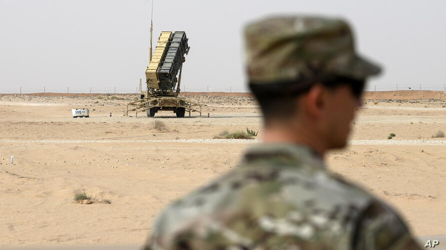 A member of the U.S. Air Force stands near a Patriot missile battery at the Prince Sultan air base in al-Kharj, central Saudi…