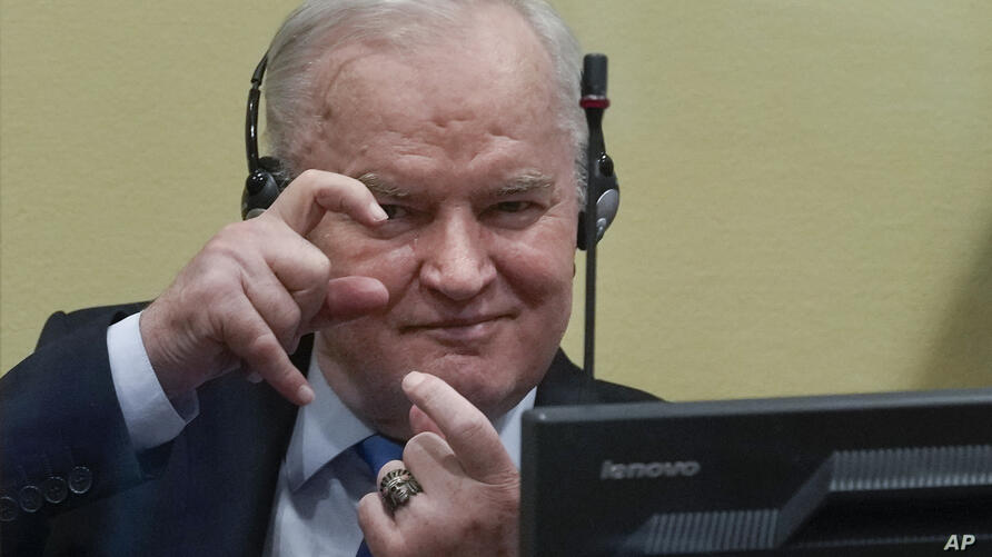 Former Bosnian Serb military chief Ratko Mladic imitates taking pictures as he sits the court room in The Hague, Netherlands,…