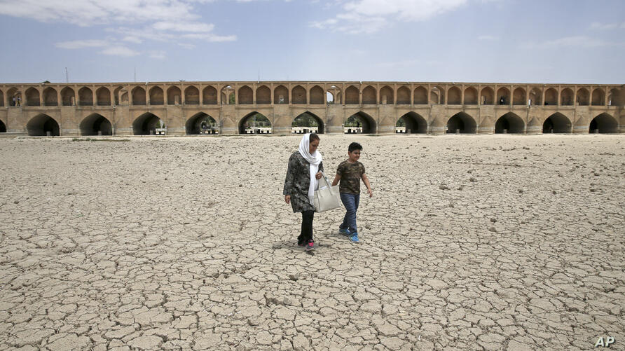 In this Tuesday, July 10, 2018 photo, a woman and a boy walk on the dried up riverbed of the Zayandeh Roud river that no longer…