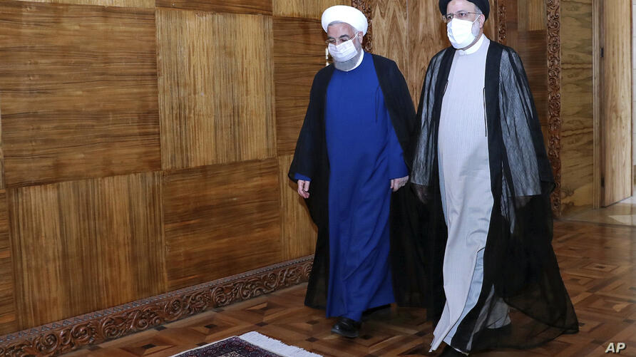 In this photo released by the official website of the office of the Iranian Presidency, President Hassan Rouhani, left, and…