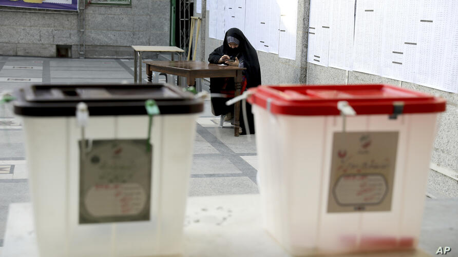 A Iranian woman sits at a polling station before it opens for presidential elections, in Tehran, Iran, Friday, June 18, 2021…