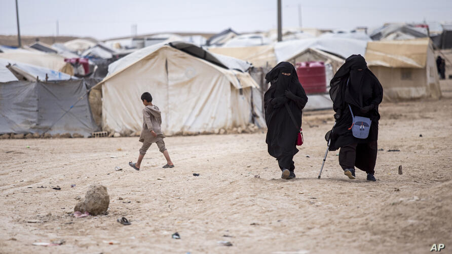 FILE - In this May 1, 2021 file photo, women walk in the al-Hol camp that houses some 60,000 refugees, including families and…