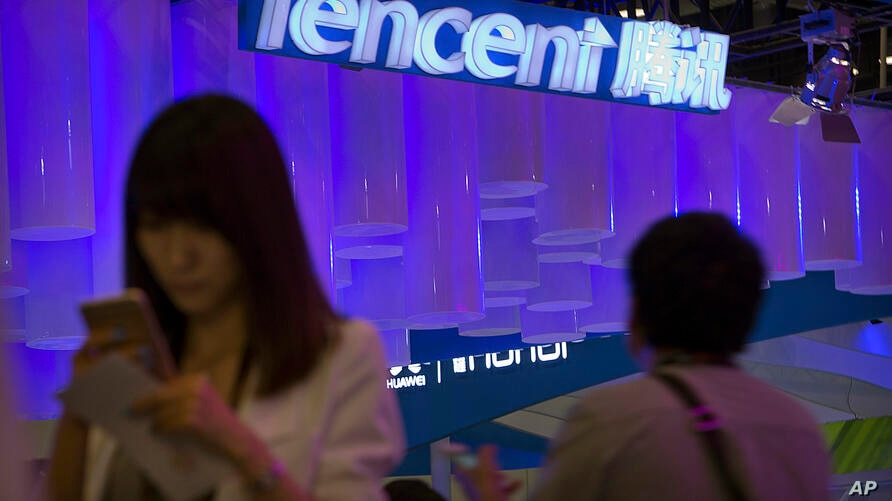 FILE - In this April 29, 2015 file photo, a woman uses her smartphone near a booth for the Chinese Internet company Tencent at…