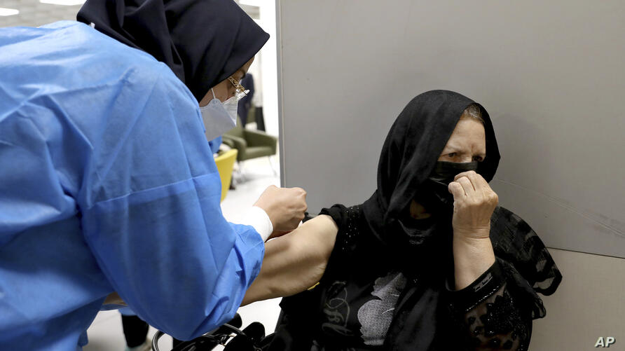 A woman reacts as she receives the Sinopharm COVID-19 vaccine at the Iran Mall shopping center in Tehran, Iran, Monday, May 17,…