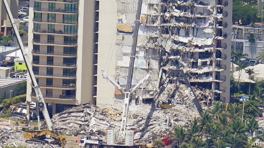 Crews work near a open tunnel, center near the bottom, in the rubble at the Champlain Towers South Condo, Sunday, June 27, 2021…