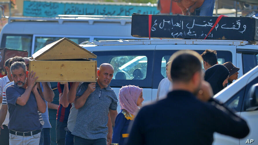 Mourners accompany victims of a Monday bombing at a Baghdad market that was busy with shoppers a day before the Muslim Eid al…