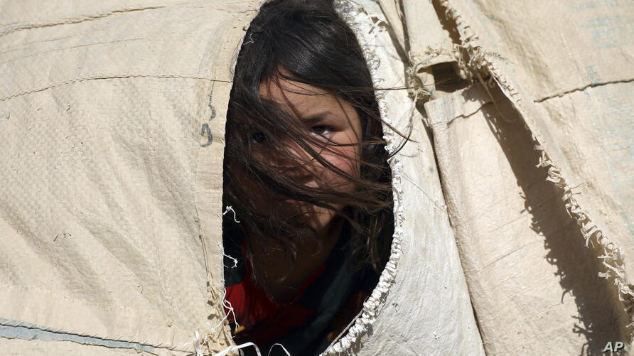An internally displaced Afghan girl who fled her home due to fighting between the Taliban and Afghan security personnel, peers…