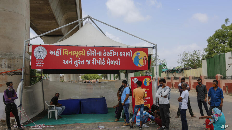 People line up to get tested for COVID-19 at a facility in Ahmedabad, India, Wednesday, June 9, 2021. Signage in Gujarati reads…