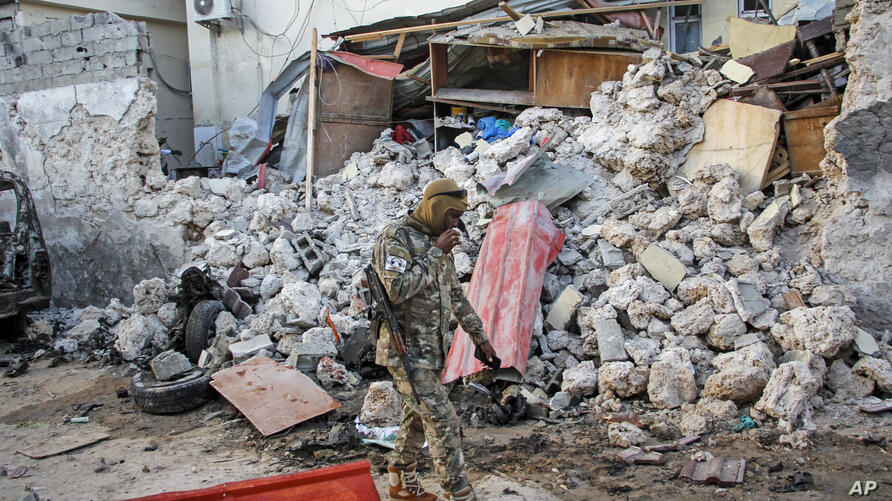 A soldier walks past wreckage in the aftermath of an attack on the Afrik hotel in Mogadishu, Somalia, Monday, Feb. 1, 2021. At…