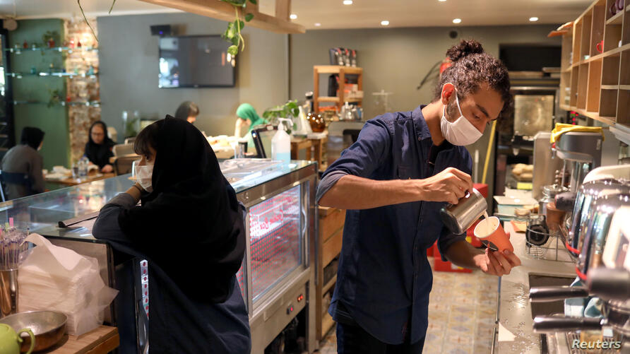 A worker wearing a protective face mask prepares a coffee at a coffee shop, following the outbreak of the coronavirus disease (COVID-19), in Tehran