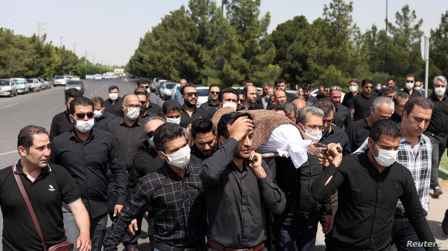 Iranians wearing protective face masks carry a coffin during a funeral ceremony, following the outbreak of the coronavirus disease (COVID-19), in Tehran