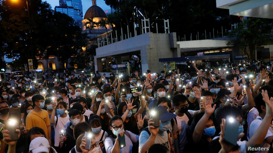 Pro-democracy demonstrators march holding their phones with flashlights on during a protest to mark the first anniversary of a mass rally against the now-withdrawn extradition bill, in Hong Kong