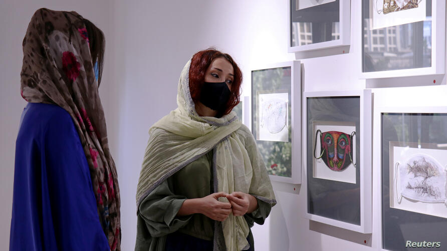 Women look at mask-themed artworks on display in an exhibition in Tehran
