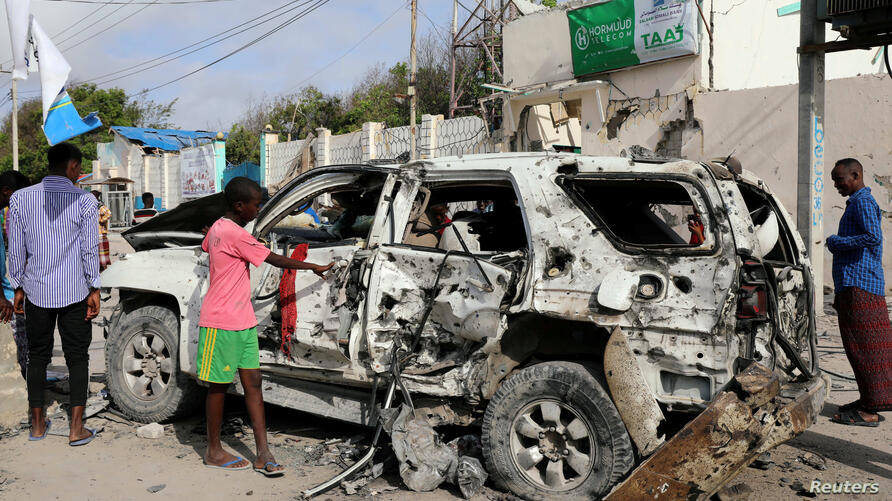 Civilians are seen near the wreckage of a car destroyed at the scene of a militant attack at the Elite Hotel in Lido beach, in Mogadishu