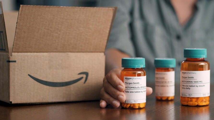 Still image from video of a person with bottles of medication with branding for Amazon Pharmacy